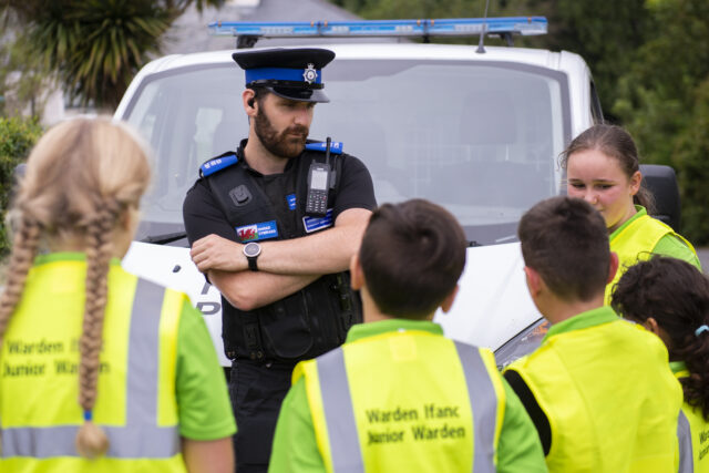 A police officer working with young volunteers